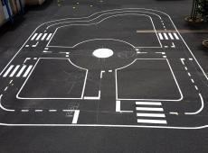 Pose de divers jeux ludiques en résine thermocollées préfabriquées (serpent alphabet, marelle, labyrinthe panda...) et réalisation d'une piste cyclable pour les tricycles, un mini terrain de football et une raquette de basketball en peinture routière.