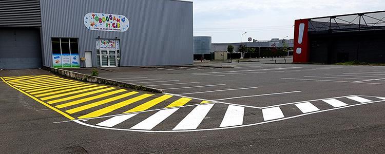 Réalisation d'un zébra en peinture routière jaune pour interdire le stationnement gênant pour les poids lourds de livraisons et réalisation d'un zébra blanc.