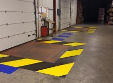 Réalisation d'un marquage en peinture routière jaune et noir de deux zébras autour de plateforme de déchargement.
